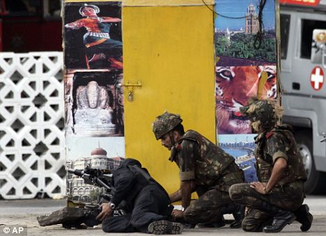 Indian forces personnel fire towards the Taj Hotel in Mumbai, India,