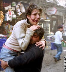 An injured woman is carried away from the British Consulate blast site in Istanbul on Thursday.